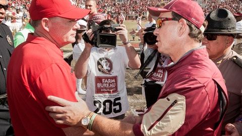 FILE - In this Oct. 17, 2015, file photo, Louisville head coach Bobby Petrino, left, and Florida State head coach Jimbo Fisher meet at midfield an NCAA college football game in Tallahassee, Fla.  Florida State's struggles during the past two seasons started to show with a 62-20 loss at Louisville last year. The Seminoles, who are off to their worst start since 1976 at 2-3, hope to avenge that loss in order to do that they must be able to stop a recent trend of not being able to contain option QBs. (AP Photo/Mark Wallheiser, File)