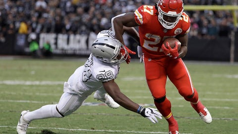 Kansas City Chiefs running back Kareem Hunt (27) is forced out of bounds by Oakland Raiders cornerback T.J. Carrie during the first half of an NFL football game in Oakland, Calif., Thursday, Oct. 19, 2017. (AP Photo/Marcio Jose Sanchez)