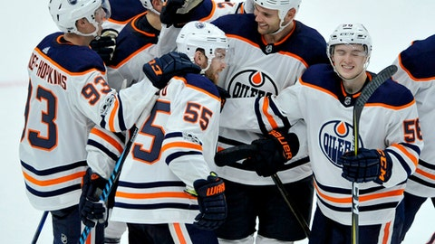 Edmonton Oilers' Mark Letestu (55) celebrates with teammates after scoring against the Chicago Blackhawks in overtime of an NHL hockey game Thursday, Oct. 19, 2017, in Chicago. The Oilers own 2-1. (AP Photo/Paul Beaty)