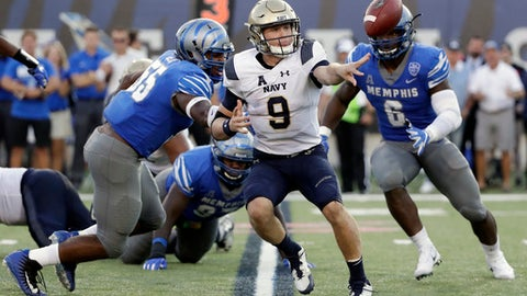FILE - In this Oct. 14, 2017, file photo, Navy quarterback Zach Abey (9) pitches the ball as he is chased by Memphis defenders Bryce Huff (55) and Genard Avery (6) in the second half of an NCAA college football game, in Memphis, Tenn. Few people have a better appreciation for option football than Central Florida coach Scott Frost. Frost and the 20th-ranked Knights will be a first-hand look at one of the nation's finest option teams, Navy, on Saturday. (AP Photo/Mark Humphrey, File)