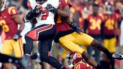 FILE - In this Saturday, Oct. 14, 2017, file photo, Utah running back Zack Moss (2) runs the ball as Southern California safety Marvell Tell III (7) tries to make the tackle during the first half of an NCAA college football game in Los Angeles. Coach Kyle Whittingham is still a hard-nosed, run-loving coach despite the new offense and he was thrilled with Moss.  (AP Photo/Kelvin Kuo, File)