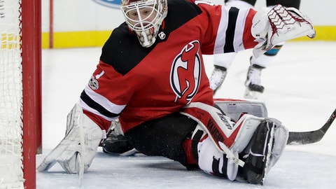 New Jersey Devils goalie Keith Kinkaid watches as a shot by the San Jose Sharks bounces off the post during the first period of an NHL hockey game, Friday, Oct. 20, 2017, in Newark, N.J. (AP Photo/Julio Cortez)