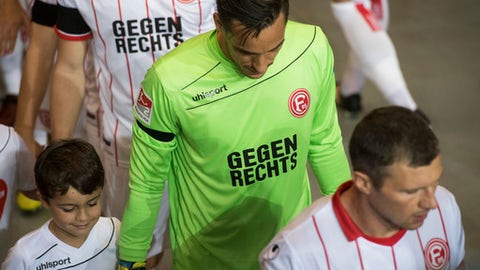 "In this Oct. 20, 2017 photo Duesseldorf's goalie Raphael Wolfand and other players wear shirts that read ""Gegen Rechts"" (against right-wing)  during the German second dvision soccer match between Fortuna Duesseldorf and Darmstadt 98, in Duesseldorf, Germany, declaring the club's opposition to far-right politics and thinking. (Bernd Thissen/dpa via AP)"