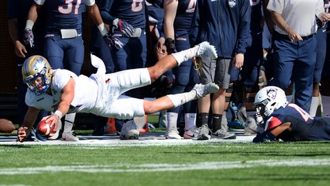 Tulsa quarterback Luke Skipper is taken down on the sidelines by Connecticut linebacker Darrian Beavers (43) during the first half of an NCAA college football game, Saturday, Oct. 21, 2017, in East Hartford, Conn. (AP Photo/Stephen Dunn)