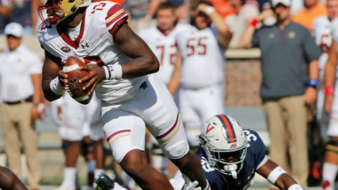 Boston College quarterback Anthony Brown (13) eludes the tackle of Virginia safety Chris Moore (39) during the first half of an NCAA college football game in Charlottesville, Va., Saturday, Oct. 21, 2017. (AP Photo/Steve Helber)
