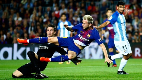 FC Barcelona's Ivan Rakitic, center, falls during the Spanish La Liga soccer match between FC Barcelona and Malaga at the Camp Nou stadium in Barcelona, Spain, Saturday, Oct. 21, 2017. (AP Photo/Manu Fernandez)