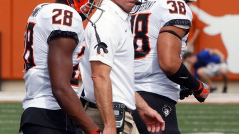 Oklahoma State head coach Mike Gundy, center, walks with his players during the first half of an NCAA college football game against Texas, Saturday, Oct. 21, 2017, in Austin, Texas. Oklahoma State won 13-10 in overtime. (AP Photo/Michael Thomas)