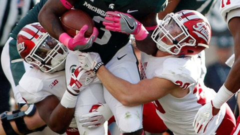 Michigan State's LJ Scott, center, is stopped by Indiana's Nathanael Snyder, left, and Chase Dutra, right, during the second quarter of an NCAA college football game, Saturday, Oct. 21, 2017, in East Lansing, Mich. (AP Photo/Al Goldis)