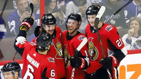 Ottawa Senators left wing Ryan Dzingel (18) celebrates his goal with teammates defenseman Chris Wideman (6) defenseman Erik Karlsson (65) and center Logan Brown (21) during second period NHL hockey action against the Toronto Maple Leafs in Ottawa on Saturday, Oct. 21, 2017. (Fred Chartrand/The Canadian Press via AP)