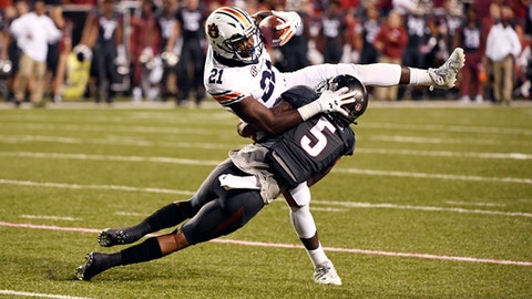 Auburn running back Kerryon Johnson (21) is tackled by Arkansas defender Henre' Toliver in the first half of an NCAA college football game in Fayetteville, Ark., Saturday, Oct. 21, 2017. (AP Photo/Michael Woods)