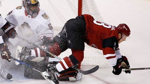 Arizona Coyotes' Christian Dvorak, right, gets sent into the air after his shot was blocked by Chicago Blackhawks' Corey Crawford, left, during the first period of an NHL hockey game Saturday, Oct. 21, 2017, in Glendale, Ariz. (AP Photo/Ross D. Franklin)