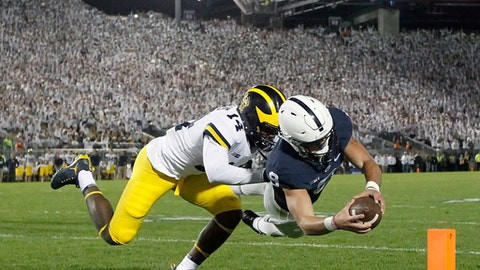 Penn State quarterback Trace McSorley (9) dives in for a touchdown as Michigan's Josh Metellus (14) defends during the second half of an NCAA college football game in State College, Pa., Saturday, Oct. 21, 2017. Penn State won 42-13. (AP Photo/Chris Knight)