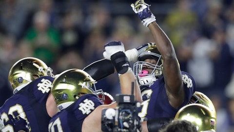 Notre Dame running back Josh Adams points skyward while lifted by teammates after one of his three touchdowns in an NCAA college football game against Southern California, Saturday, Oct. 21, 2017, in South Bend, Ind. (AP Photo/Carlos Osorio)