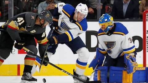 St. Louis Blues goalie Jake Allen, right, blocks a shot by Vegas Golden Knights right wing Pierre-Edouard Bellemare, left, during the third period of an NHL hockey game Saturday, Oct. 21, 2017, in Las Vegas. Blues defenseman Carl Gunnarsson is in the middle. (AP Photo/John Locher)