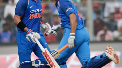 India's captain Virat Kohli, left, and Mahendra Singh Dhoni run between the wickets during their first one-day international cricket match against New Zealand in Mumbai, India, Sunday, Oct. 22, 2017. (AP Photo/Rafiq Maqbool)