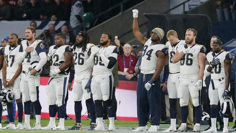 Los Angeles Rams outside linebacker Robert Quinn (94) raises his fist as the national anthem is played before an NFL football game between the Los Angeles Rams and the Arizona Cardinals at Twickenham Stadium in London, Sunday Oct. 22, 2017. (AP Photo/Tim Ireland)