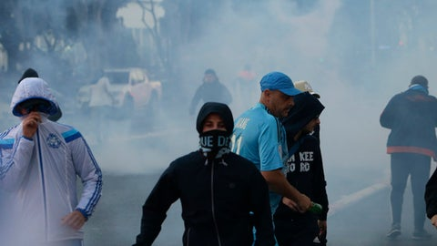 Supporters fight with the police before the League One soccer match between Marseille and Paris Saint-Germain, at the Velodrome stadium, in Marseille, southern France, Sunday, Oct. 22, 2017. (AP Photo/Claude Paris)