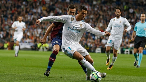 Real Madrid's Cristiano Ronaldo, front, vies for the ball with Eibar's Gonzalo Escalante during the Spanish La Liga soccer match between Real Madrid and Eibar at the Santiago Bernabeu stadium in Madrid, Sunday, Oct. 22, 2017. (AP Photo/Francisco Seco)