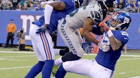 New York Giants' Eli Apple, left, and Darian Thompson, right, break up a pass intended for Seattle Seahawks' Tyler Lockett, center, during the first half of an NFL football game, Sunday, Oct. 22, 2017, in East Rutherford, N.J. (AP Photo/Bill Kostroun)