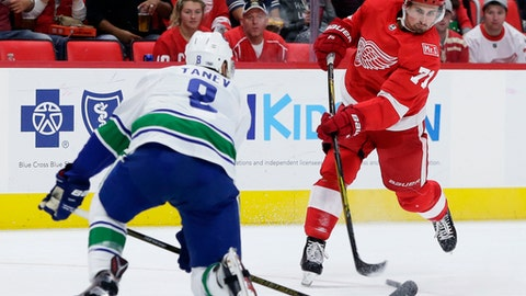 Detroit Red Wings center Dylan Larkin (71) takes a shot on goal against Vancouver Canucks defenseman Christopher Tanev (8) during the second period of an NHL hockey game, Sunday, Oct. 22, 2017, in Detroit. (AP Photo/Duane Burleson)