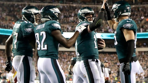 Philadelphia Eagles quarterback Carson Wentz, second from right, and tight end Zach Ertz, far right, celebrate after they connected on a touchdown pass during the first half of an NFL football game against the Washington Redskins, Monday, Oct. 23, 2017, in Philadelphia. Teammates Alshon Jeffery, left, and Torrey Smith join in the celebration. (AP Photo/Michael Perez)