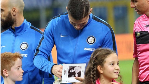 Inter's captain Mauro Icardi signs  Anne Frank's diary for a child, prior the Italian Serie A soccer match between Inter and Sampdoria at the San Siro stadium in Milan, Italy, Tuesday Oct. 24, 2017. Anne Frank's diary will be read aloud at all soccer matches in Italy this week, the Italian soccer federation announced Tuesday after shocking displays of anti-Semitism by fans of the Rome club Lazio. (Matteo Bazzi/ANSA via AP)