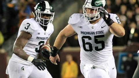 FILE - In this Saturday, Oct. 14, 2017, file photo, Michigan State running back L.J. Scott (3) runs with blocking from guard Brian Allen (65) during the third quarter of an NCAA college football game against Minnesota in Minneapolis. Michigan State has exceeded expectations this year, but there's probably a limit to how much the 16th-ranked Spartans can accomplish if their offense doesn't start pulling its weight.  (AP Photo/Andy Clayton-King, File)