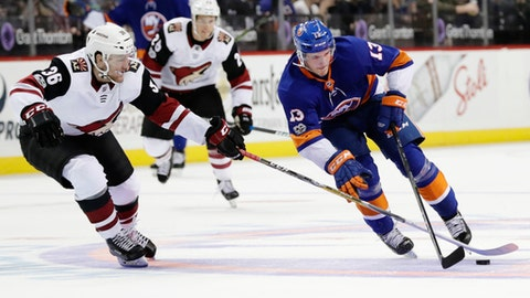 Arizona Coyotes' Christian Fischer (36) fights for control of the puck with New York Islanders' Mathew Barzal (13) during the second period of an NHL hockey game Tuesday, Oct. 24, 2017, in New York. (AP Photo/Frank Franklin II)