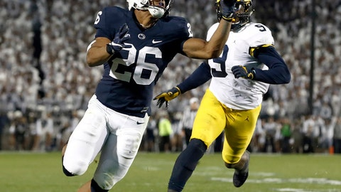 FILE - In this Saturday, Oct. 21, 2017, file photo, Penn State's Saquon Barkley (26) gains control of a pass and takes it in for a touchdown against Michigan during the second half of an NCAA college football game in State College, Pa. Three days before the first College Football Playoff rankings of the season are released Penn State and Ohio State will play a game, Saturday, Oct. 28, that could complicate the selection committee's task down the road, if the Buckeyes win. (AP Photo/Chris Knight, File)