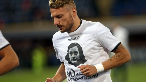 """Lazio's Ciro Immobile wears a t-shirt with an image of Anna Frank and reading in Italian """" No to Anti-semitism """" prior to the Serie A soccer match between Lazio and Bologna at the Renato Dall'Ara stadium in Bologna, Italy, Wednesday, Oct. 25, 2017.  Anne Frank's diary will be read aloud at all soccer matches in Italy this week, the Italian soccer federation announced Tuesday after shocking displays of anti-Semitism by fans of the Rome club Lazio. Lazio supporters on Sunday littered the Stadio Olimpico in Rome with images of Anne Frank, the young diarist who died in the Holocaust, wearing a jersey of city rival Roma. The ultra right-wing fans of Lazio associate their Roma counterparts with being left-wing and Jewish, and had hoped to incite Roma fans, since the teams share the same stadium. (Giorgio Benvenuti/ANSA via AP)"""