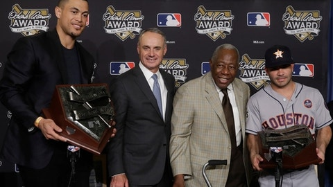 Miami Marlins' Giancarlo Stanton and Jose Altuve post with Hank Aaron and MLB Commissioner Rob Manfred after winning their league's Hank Aaron Award at baseball's World Series Wednesday, Oct. 25, 2017, in Los Angeles. (AP Photo/Alex Gallardo)