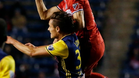 Chicago Fire forward Luis Solignac, top, heads the ball under pressure from New York Red Bulls defender Gideon Baah during the first half of an MLS soccer playoff game, Wednesday, Oct. 25, 2017, in Bridgeview, Ill. (AP Photo/Nam Y. Huh)