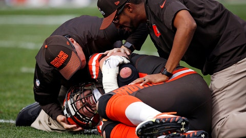 FILE - In this Sunday, Oct. 22, 2017, file photo, trainers, top, check Cleveland Browns tackle Joe Thomas after Thomas was hurt in the second half of an NFL football game against the Tennessee Titans in Cleveland. In an instant, while blocking on a routine running play he had completed thousands of times without incident or injury, Thomas' season ended and his career met an unexpected crossroads. Without warning, a remarkable run of durability was over. (AP Photo/Ron Schwane, File)