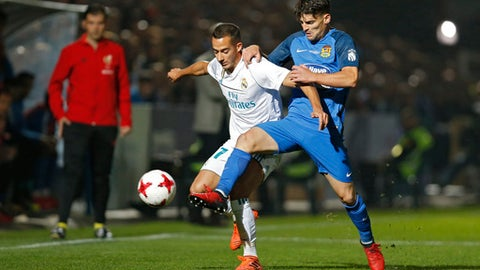 Real Madrid's Lucas Vazquez, left, tussles for the ball with Fuenlabrada's Fran Garcia during a Spanish Copa del Rey round of 32 first leg soccer match between Fuenlabrada and Real Madrid at the Fernando Torres stadium in Fuenlabrada, outside Madrid, Thursday, Oct. 26, 2017. (AP Photo/Francisco Seco)
