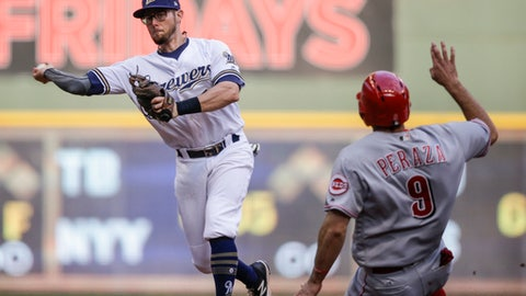 """FILE - In this Thursday, Sept. 28, 2017 file photo, Milwaukee Brewers' Eric Sogard throws to first after forcing out Cincinnati Reds' Jose Paraza at second during the sixth inning of a baseball game in Milwaukee. The Milwaukee Brewers have signed infielder Eric Sogard to a one-year contract. He was eligible to become a free agent after the World Series. General manager David Stearns said Thursday, Oct. 26, 2017 that Sogard provides a """"veteran presence"""" and is someone who can play several positions and get on base often.(AP Photo/Tom Lynn, File)"""