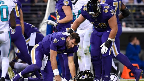 Baltimore Ravens quarterback Joe Flacco (5) is assisted by offensive guard Matt Skura after colliding with Miami Dolphins middle linebacker Kiko Alonso in the first half of an NFL football game, Thursday, Oct. 26, 2017, in Baltimore. (AP Photo/Gail Burton)