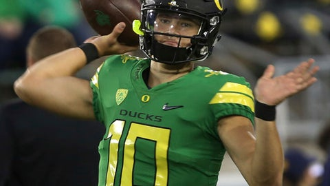 FILE - In this Sept. 30, 2017, file photo, Oregon quarterback Justin Herbert warms up before an NCAA college football game against California in Eugene, Ore. While the injured Herbert's appearance in pads at practice this week is tantalizing, it's more likely that true freshman Braxton Burmeister will make his fourth straight start against Utah in Eugene, Ore., Saturday, Oct. 28, 2017, as the Ducks try to turn their season around. (AP Photo/Chris Pietsch, File)