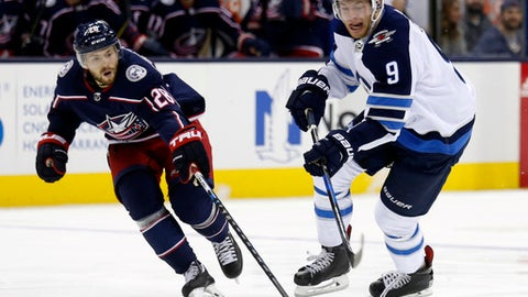 Winnipeg Jets forward Andrew Copp, right, chases the puck against Columbus Blue Jackets forward Oliver Bjorkstrand, of Denmark, during the first period of an NHL hockey game in Columbus, Ohio, Friday, Oct. 27, 2017. (AP Photo/Paul Vernon)
