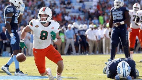 Miami's Braxton Berrios (8) celebrates his touchdown in the end zone while North Carolina's Myles Wolfolk (11) reacts during the second half of an NCAA college football game in Chapel Hill, N.C., Saturday, Oct. 28, 2017. Miami won 24-19. (AP Photo/Gerry Broome)