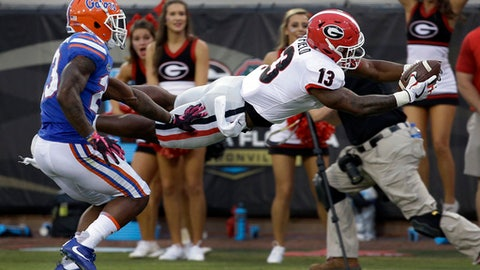 Georgia running back Elijah Holyfield (13) dives over the goal line in front of Florida defensive back Chauncey Gardner Jr. to compete a 39-yard touchdown run in the second half of an NCAA college football game, Saturday, Oct. 28, 2017, in Jacksonville, Fla. Georgia won 42-7. (AP Photo/John Raoux)