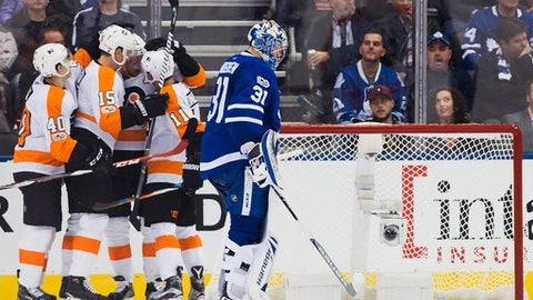 Toronto Maple Leafs goalie Frederik Andersen (31) pushes the puck out of the net as Philadelphia Flyers players celebrate their goal during the second period of an NHL hockey game in Toronto on Saturday, Oct. 28, 2017. (Nathan Denette/The Canadian Press via AP)