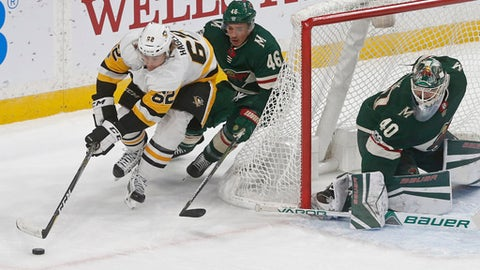 Minnesota Wild's Jared Spurgeon (46) chases Pittsburgh Penguins' Carl Hagelin, left, of Sweden, around the net as Wild goalie Devan Dubnyk watches the play during the second period of an NHL hockey game Saturday, Oct. 28, 2017, in St. Paul, Minn. (AP Photo/Jim Mone)