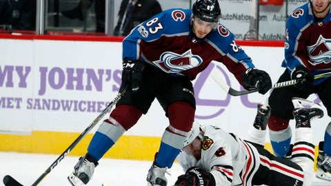 Chicago Blackhawks defenseman Michal Kempny, back, of the Czech Republic, uses his stick to break up a pass for Colorado Avalanche left wing Matt Nieto in the third period of an NHL hockey game Saturday, Oct. 28, 2017, in Denver. The Avalanche won 6-3. (AP Photo/David Zalubowski)