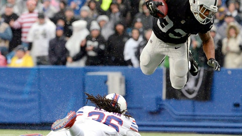 As rain falls, Oakland Raiders running back DeAndre Washington, right, goes airborne after being hit by Buffalo Bills defensive back Trae Elston during the first half of an NFL football game, Sunday, Oct. 29, 2017, in Orchard Park, N.J. (AP Photo/Adrian Kraus)