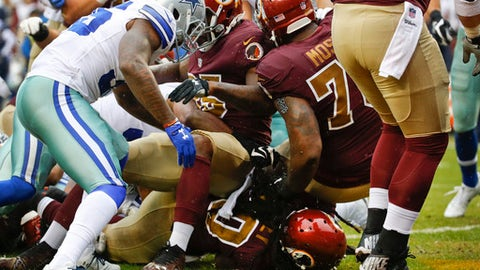 Washington Redskins running back Rob Kelley (20) (bottom) plows through the line to score a touchdown during the first half of an NFL football game against the Dallas Cowboys in Landover, Md., Sunday, Oct. 29, 2017. (AP Photo/Patrick Semansky)
