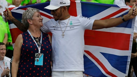 Mercedes driver Lewis Hamilton, of Britain, celebrates with his mother Carmen Larbalestier at the pit lane after the Formula One Mexico Grand Prix auto race at the Hermanos Rodriguez racetrack in Mexico City, Sunday, Oct. 29, 2017. Hamilton won his fourth career Formula One season championship on Sunday with a ninth-place finish at the Mexican Grand Prix in a race won by Red Bull's Max Verstappen. (AP Photo/Rebecca Blackwell)
