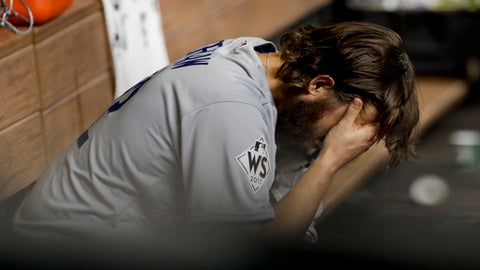 Los Angeles Dodgers starting pitcher Clayton Kershaw sits in the dugout after Houston Astros' Yuli Gurriel hit a three-run home run during the fourth inning of Game 5 of baseball's World Series Sunday, Oct. 29, 2017, in Houston. (AP Photo/Matt Slocum)