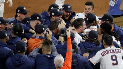 Houston Astros' Alex Bregman is mobbed by teammates after hitting in the game-winning run during the 10th inning of Game 5 of baseball's World Series against the Los Angeles Dodgers Monday, Oct. 30, 2017, in Houston. The Astros won 13-12 to take a 3-2 lead in the series. (AP Photo/Eric Gay)