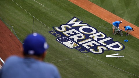 A fan watches as workers paint the World Series baseball logo on the field at Dodger Stadium ahead of Tuesday's Game 6 of baseball's World Series between the Los Angeles Dodgers and the Houston Astros, Monday, Oct. 30, 2017, in Los Angeles. (AP Photo/Jae C. Hong)