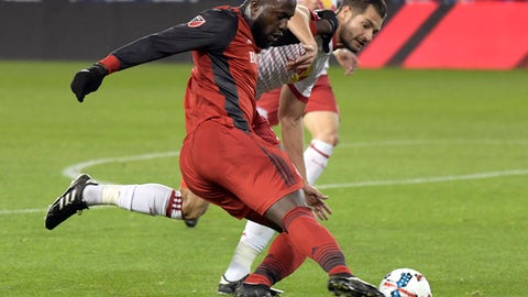 Toronto FC forward Jozy Altidore, left, passes the ball by New York Red Bulls defender Damien Perrinelle, right, during the first half of an MLS Eastern Conference semifinal soccer match Monday, Oct. 30, 2017, in Harrison, N.J. (AP Photo/Bill Kostroun)
